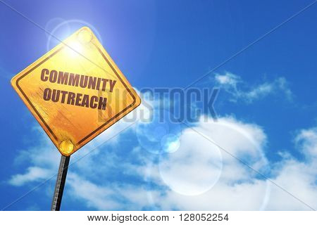 Yellow road sign with a blue sky and white clouds: Community outreach