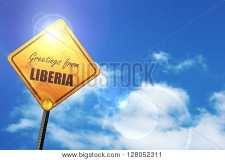 Yellow road sign with a blue sky and white clouds: Greetings from liberia