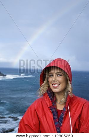 Caucasian mid-adult woman in red raincoat in front of ocean with rainbow in background looking at viewer and smiling in Maui, Hawaii.