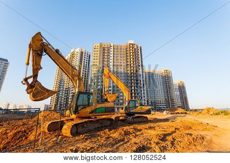 two excavators and a new multistorey building on a background of blue sky