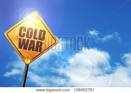 Yellow road sign with a blue sky and white clouds: cold war
