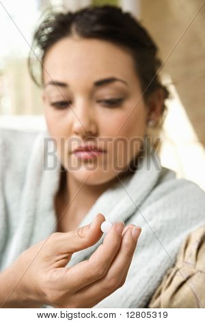 Caucasian/Hispanic young woman in bathrobe holding pill in hand.