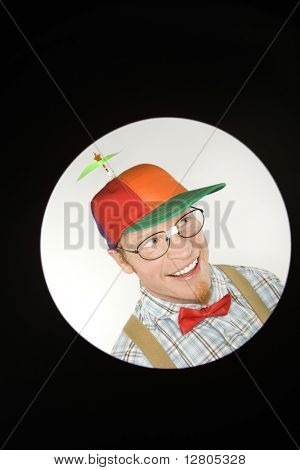 Close up circle vignett of Caucasian young man dressed like nerd wearing propeller hat looking mischievous.