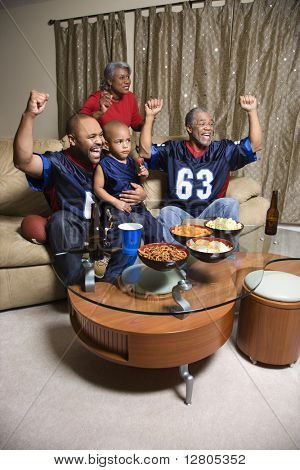 A three generation African-American family cheering and watching football game together on tv.