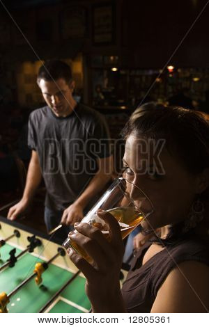 Young woman drinking beer and looking at viewer while man plays foosball in pub.