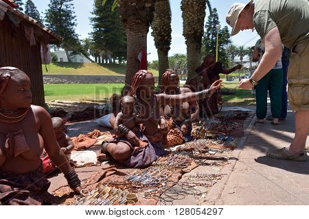 SWAKOPMUND NAMIBIA - JAN 31 2016 - Himba woman sales handmade jewelery to europian tourist. Women hair painted with a layer of clay loam. Himba is an ethnic group living in northern Namibia