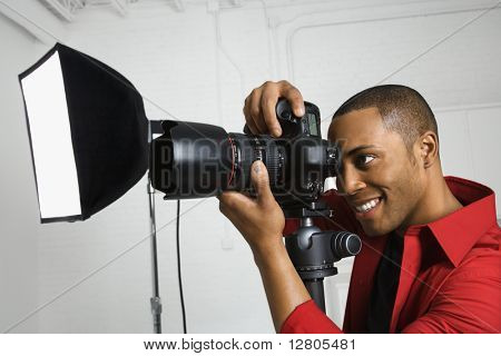 African American young male adult looking through camera on tripod.