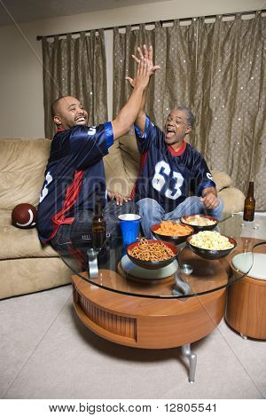 African-American father and son giving high five while watching football game.