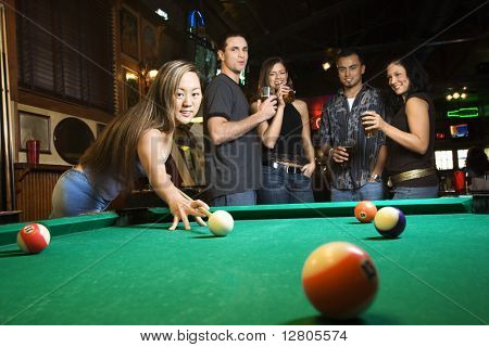 Young asian woman preparing to hit pool ball while playing billiards.