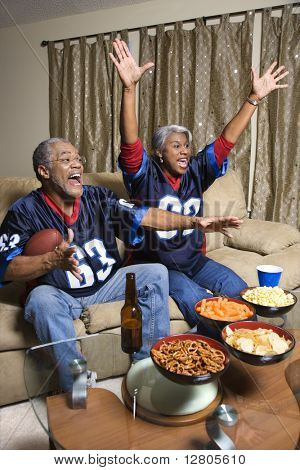 Middle-aged African-American couple cheering and watching football game.