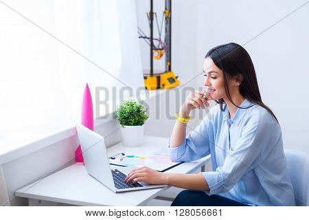 Do everything with eagerness. Cheerful  beautiful delighted woman sitting at the table and using laptop while expressing joy
