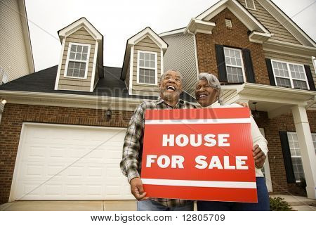 Portrait of middle-aged African-American couple outside house with for sale sign.