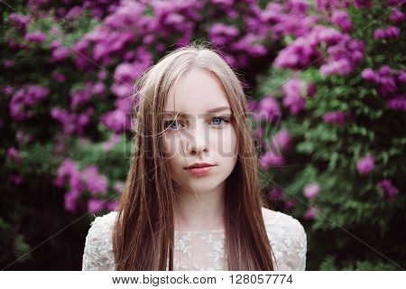 Beautiful young girl in a flowering lilac. Garden of lilac bloom