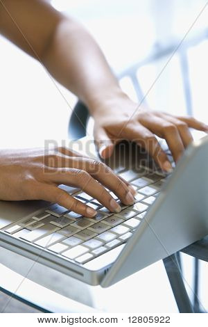 Asian/Indian young womans hands typing on laptop keyboard.