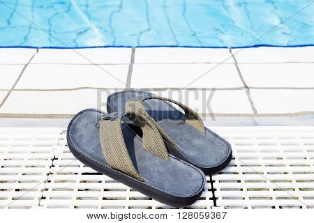 canvas flip flops beside a blue pool