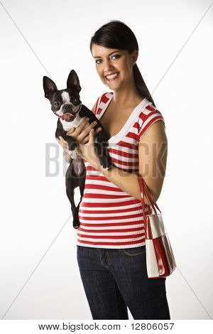 Young adult female Caucasian holding Boston Terrier dog.