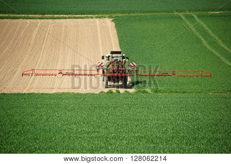 A tractor spraying a corn field with chemical fertilizers.