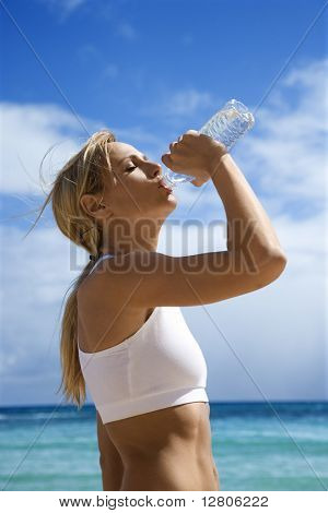 Caucasian young adult woman drinking water on beach.