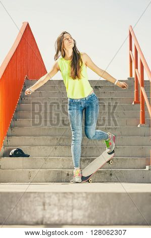 Cool skate young long haired girl riding skateboard on the urban stairs. Active lifestyle funky in summer. Outdoor trendy sport teen.