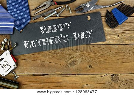 Happy Father's Day Written On Slate With Corner Border Of Tools On Old Wood Background