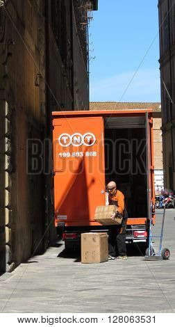 SIENA ITALY - CIRCA APRIL 2016: TNT post van parked in A Street Of The City Centre With Postman Downloading Parcels