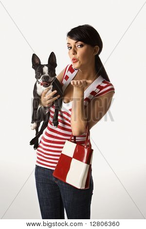 Young adult female Caucasian holding Boston Terrier.