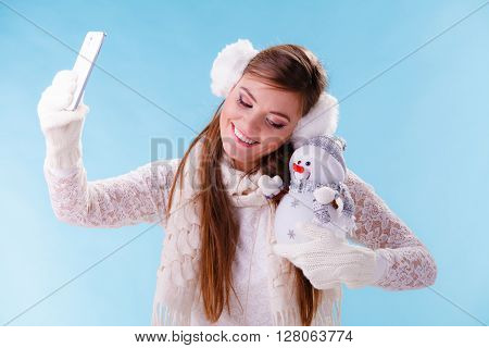 Smiling pretty cute woman holding little snowman taking selfie self photo picture with camera. Attractive girl in earmuffs and white sweater pullover in studio on blue. Winter fashion.