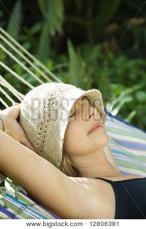 Caucasian mid-adult woman napping in hammock.