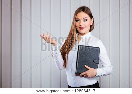 Career business work in office. Young woman in formal wear hold case with files documents paperwork presenting gesture.