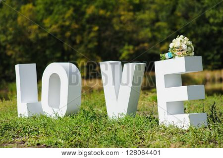 Big wood white letters Love letters on a background of green park. Beautiful wedding bouquet tied with white lace and blue ribbon on big e letter. Forest and river in the background.