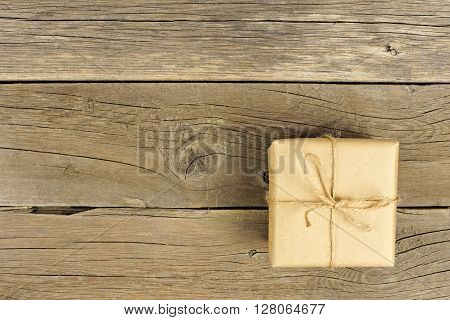 Brown Paper Wrapped Gift Box With Twine Bow On A Rustic Wood Background
