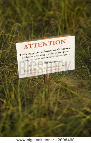 Beach access stay off dunes warning sign.