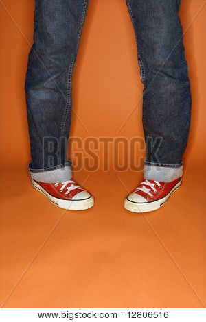 Person in jeans and sneakers with feet turned inward.