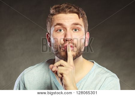Young man guy with finger on lips showing hand quiet silence sign gesture in studio on black.