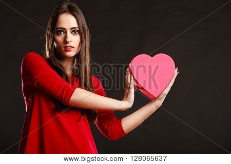 Charity and sharing concept. Love and feelings. Young pretty woman in red clothes holding heart box present gift on grey background in studio.