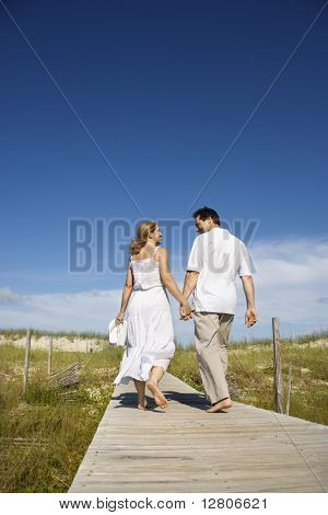 Caucasian mid-adult couple holding hands walking down beach access path.
