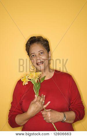 Afroamerikaner reife Erwachsene Weibchen halten Blumen.