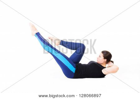 Young woman doing abs exercise at photo studio