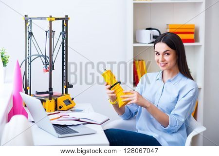 Full of positive emotions.  Pleasant beautiful smiling delighted woman sitting at the table and holding model printed on the 3dprinter while expressing gladness