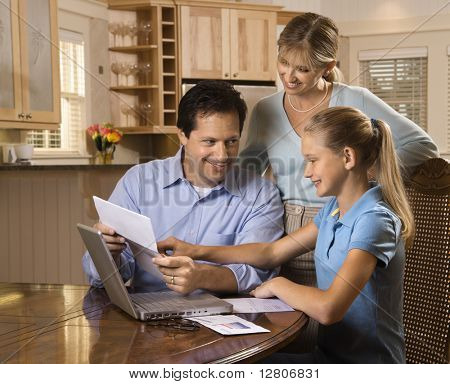 Caucasian family paying bills on laptop computer.