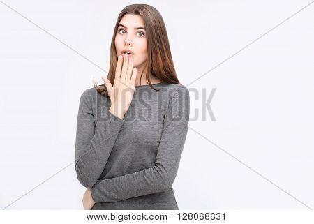 Portrait of surprised woman in grey dress