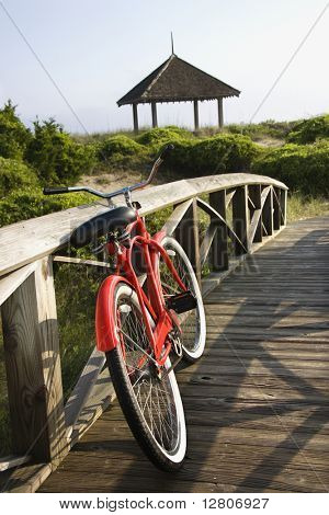 Image of red bike leaned up against railing of boardwalk.