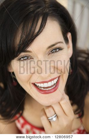 Mid-adult Caucasian woman smiling wearing wedding ring.
