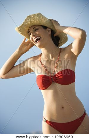 Caucasian mid-adult female in swimsuit holding hat on head laughing.
