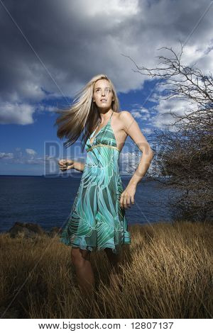 Caucasian young adult blond woman standing in field on coast with hair swinging out.