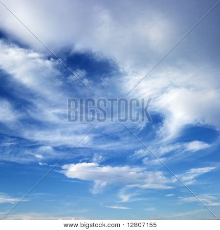 Wispy cloud formations against clear blue sky.