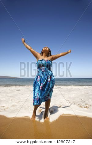 Yound-adult Black woman standing in shore with arms stretched.