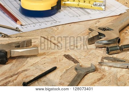 The working tools for construction and repair of house: tape measure (yardstick), wrench, screwdriver, pliers, spanner, screw, pencil. Photos with limited depth of field.
