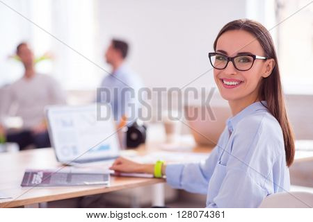 Full of gladness. Cheerful charming nice  woman smiling and  sitting at the table while working on the laptop