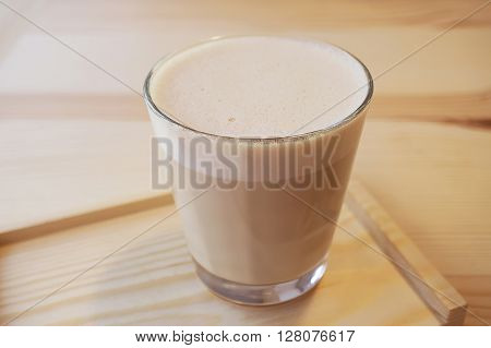 Glass cup of cappuccino on a wooden background